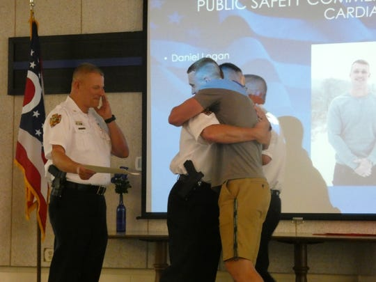 Newark police Deputy Chief Darrin Logan embraces his son, Daniel Logan, at the annual Newark Division of Police Awards Presentation on Wednesday, May 29, 2019. Chief Barry Connell wipes his cheek, preparing to hand Daniel Logan a certificate for saving his father's life during a heart attack earlier this year.