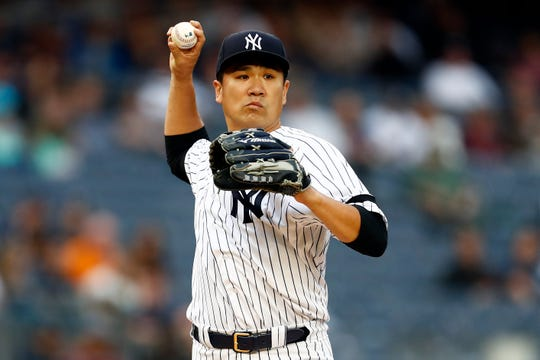 May 28, 2019; Bronx, NY, USA; New York Yankees pitcher Masahiro Tanaka (19) throws to first base against the San Diego Padres during the first inning at Yankee Stadium.