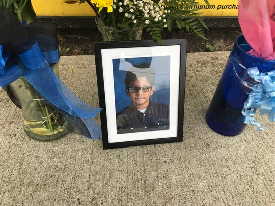 A framed photo of 10-year-old Alvin Marcallo is part of a makeshift memorial near the corner of West Church Street and Veterans Plaza in Bergenfield that was created after his death on Memorial Day.
