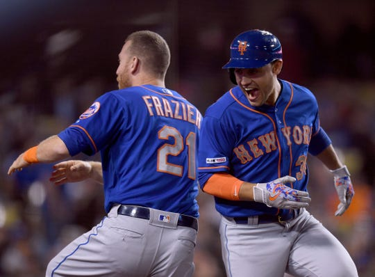Michael Conforto, right,  of the New York Mets celebrates his first career grand slam with Todd Frazier #21, to take a 6-2 lead over the Los Angeles Dodgers, during the seventh inning at Dodger Stadium on May 28, 2019 in Los Angeles, California.