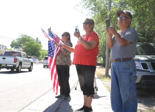 From left, Anita Hayes, Rita Belin and Lorenzo Garnenez stand along U.S. Highway 64 in Shiprock to watch the procession for the late state Sen. John Pinto on May 29.