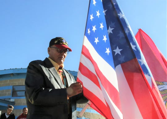 Waterflow resident Tommy Nelson unrolls his United States flag before the motorcade for the late state Sen. John Pinto arrives on May 29 to the Shiprock Chapter house in Shiprock.