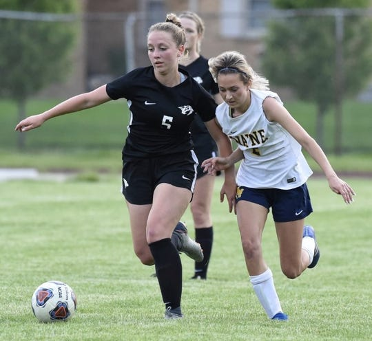 Plymouth's Morgan Buroker fends off Wayne defender Brooke Estepp.