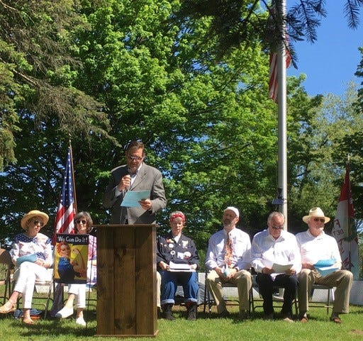 At the Memorial Day ceremony at  historic Franklin Cemetery, Ingo Rautenberg reads the Gettysburg Address while (from left) Eileen Pulker, Margaret Mathis, Donnaleen Lanktree, Rev. David Huseltine, and Seven Bancroft listen. They are the participants in the event. Not shown, Ted Spicer.  The audience felt a deep appreciation of the patriotic event honoring the service of veterans.