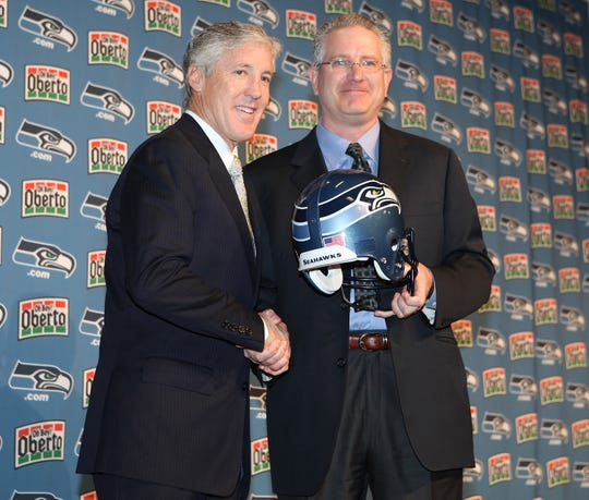 Tod Leiweke, former CEO of the Seattle Seahawks (right), presents new head coach Pete Carroll a Seahawks helmet during a news conference on Jan. 12, 2010.