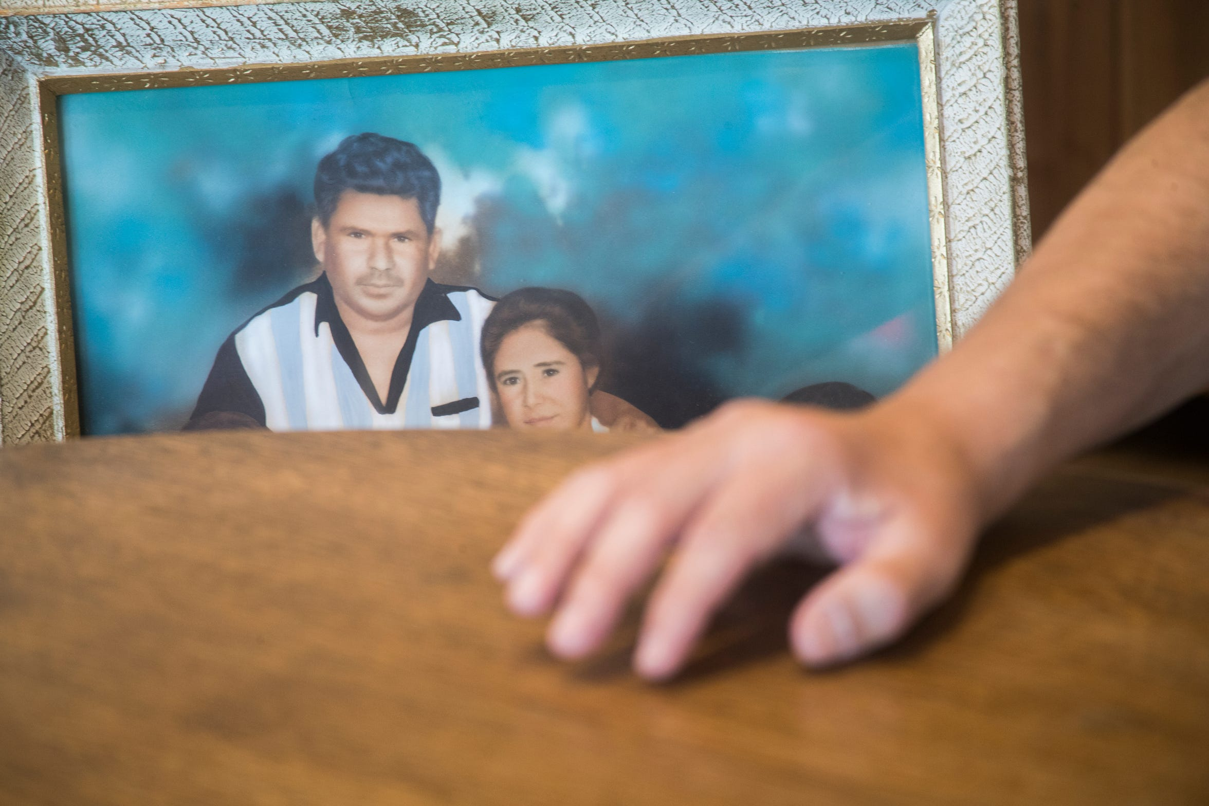Jesus Manuel Guzman studies a painting of his parents, Manuel Mendoza and Guadalupe Guzman. Manuel died in the 1974 farmworker bus crash.