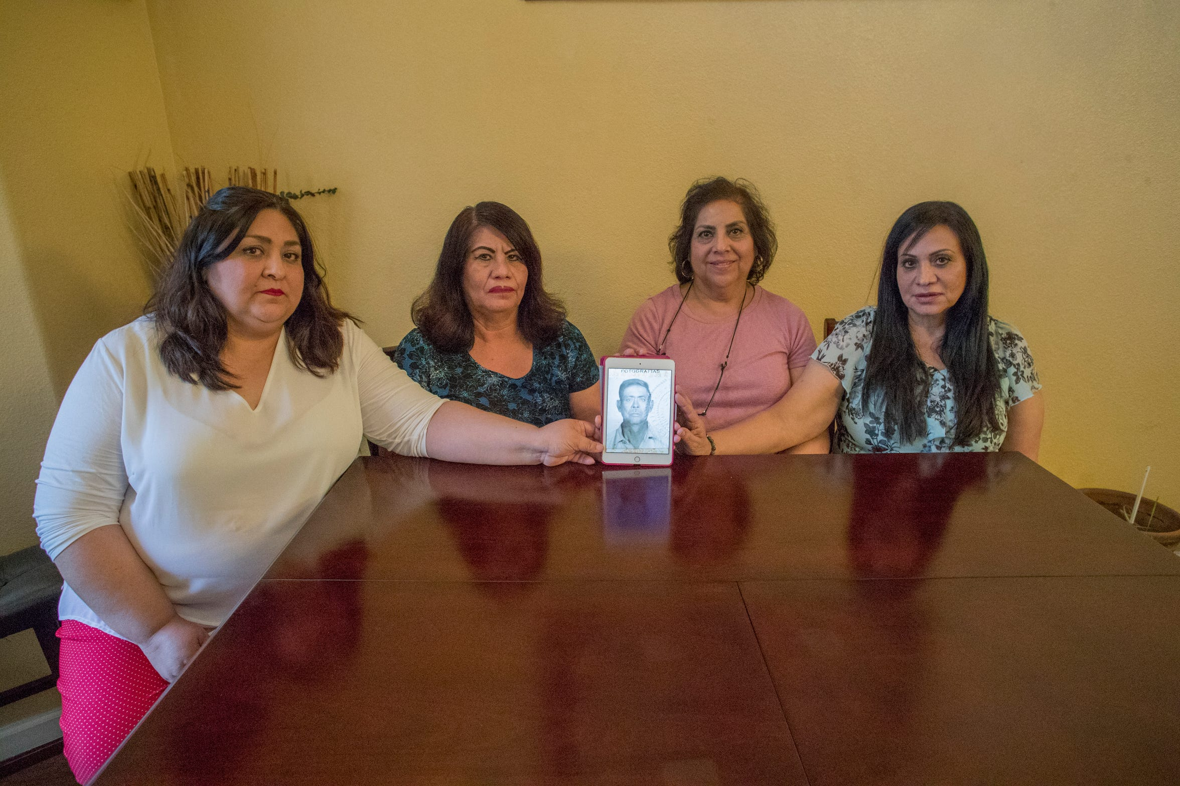 From left, sisters, Yoana Barraza, Lucia Cardenas, Catalina Cesario and Maria Cardenas hold a photo on an iPad of their father, Librado Cardenas Zazueta, who died along with 18 others in an accident aboard a farmworker bus en route to Blythe on January 15, 1974. The sisters now live in California.