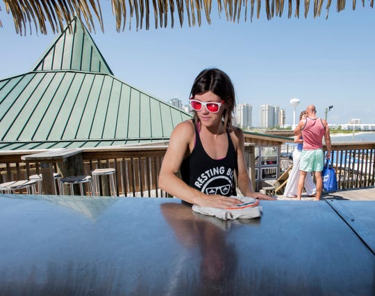 Bartender Kelly Hagen gets the deck bar ready for business at Juana's Pagodas and Sailors' Grill at Navarre Beach on Wednesday, May 29, 2019. The longtime Navarre Beach business is celebrating it's 30th anniversary this year.