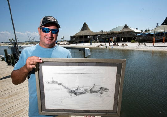 Juana's Pagodas general manager and a part owner, Kevin Rudzki, shows off and the initial plan of the Navarre Beach entertainment complex against the backdrop of how it looks today on May 29, 2019. The longtime Navarre Beach business is celebrating it's 30th anniversary this year.