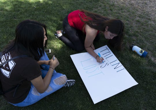 Lisett Montano (left), 16, and Ximena Arroyo, 16, make signs of support for their DACA friends at the Arizona state Capitol.