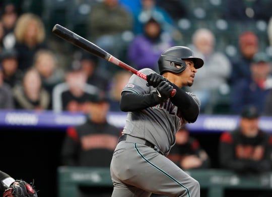 Arizona Diamondbacks' Eduardo Escobar follows the flight of his solo home run off Colorado Rockies starting pitcher Antonio Senzatela in the third inning of a baseball game Tuesday, May 28, 2019, in Denver.