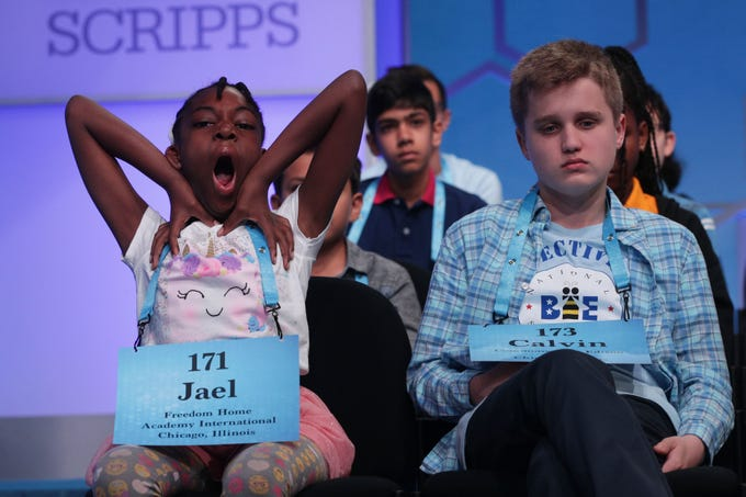 Jael Green of Chicago, Illinois, yawns as she waits for her turn to spell during round three of the Scripps National Spelling Bee at the Gaylord National Resort & Convention Center.