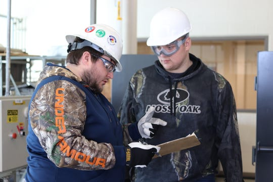 Chemical processing apprentices Timothy Bond, left, and Trent Oldenburg discuss a reaction's progression in the Delta College lab.