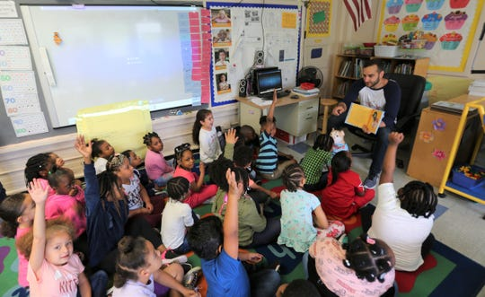 Jason Kraus (right) answers questions about a book he published to two Kindergarten classes at Early Learning Center in the City of Poughkeepsie on Wednesday, May 29, 2019.