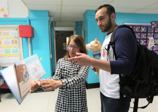 Lori Kraus shows her son Jason Kraus (right) how to properly read his book to young children at Early Learning Center in the City of Poughkeepsie on Wednesday, May 29, 2019.