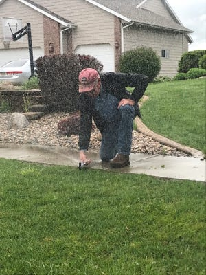 Paul Clancy of Paul's Always Green Lawn Sprinklers checks a sprinkler on Country Club Avenue on Wednesday, May 29 in Brandon.