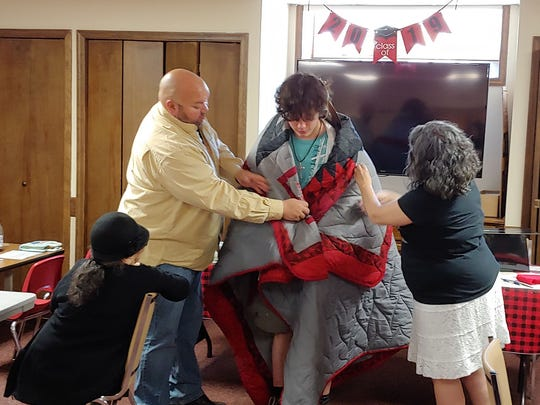 Miles Livermont is presented with a star quilt before his graduation by Mona DuBray, Ross DuBray and Donita DuBray Fischer.