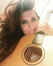Lisa Landucci holds a guitar.