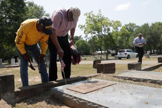 Frank Williams, a member of the Buffalo Soldiers, left, and Congressman Al Lawson place an American flag at the grave of a veteran buried in Greenwood Cemetery Wednesday, May 29, 2019. It was brought to the city's attention that the veterans were not honored with a flag for Memorial Day.