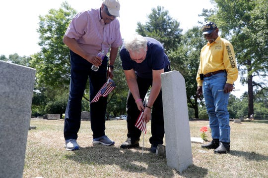 Congressman Al Lawson, left, and Jon Ausman, former Florida Democratic Party vice-chair, place an American flag at the grave of a veteran buried in Greenwood Cemetery while Frank Williams, a member of the Buffalo Soldiers, watches Wednesday, May 29, 2019. It was brought to the city's attention that the veterans were not honored with a flag for Memorial Day.