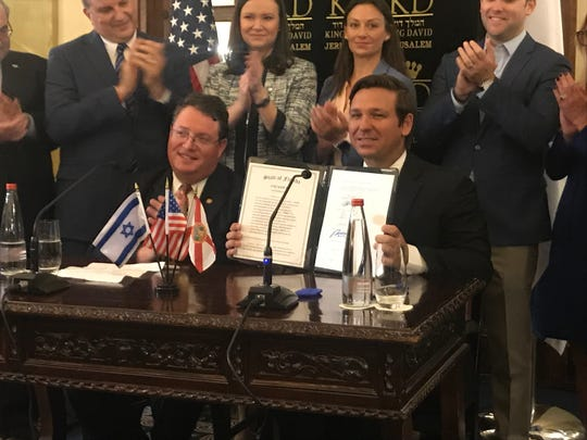 Rep. Randy Fine sits with Florida Gov. Ron DeSantis as others watch him sign state anti-Semitism bill in the King David