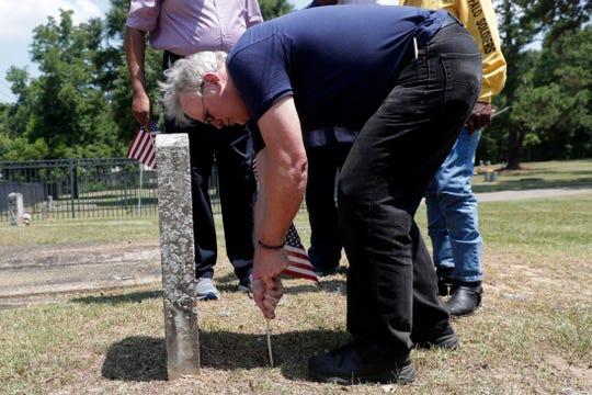 Jon Ausman, former Florida Democratic Party vice-chair, places an American flag at the grave of a veteran buried in Greenwood Cemetery Wednesday, May 29, 2019. It was brought to the city's attention that the veterans were not honored with a flag for Memorial Day.