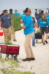 Ray Wood, a Duke Energy engineer from Perry, Florida, plants sea oats at St. George Island as part of a volunteer effort.