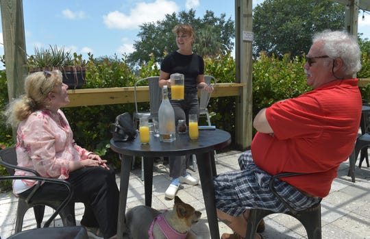 "Sherry Taylor (left) and her husband Frank Eichas (right), of Stuart, talk with farm manager Hannah Brock, filling in as server, while enjoying drinks after lunch at the patio of Ground Floor Farm on Sunday, May 26, 2019 in Stuart. ""This place is so amazing, they have live bees that make the honey here, they have chickens that lay eggs for breakfast, they have vegetables here that we eat from farm to table, who could ask for more. It's amazing,"" Taylor said."