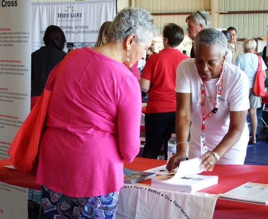 Volunteer Margaret Fook, right, shares information with a guest on the American Red Cross' Pillowcase Project, which teaches children about emergency preparedness.