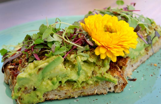 Avocado toast is garnished with a flower and served at The Royal Egg Cafe in Westlake Village.