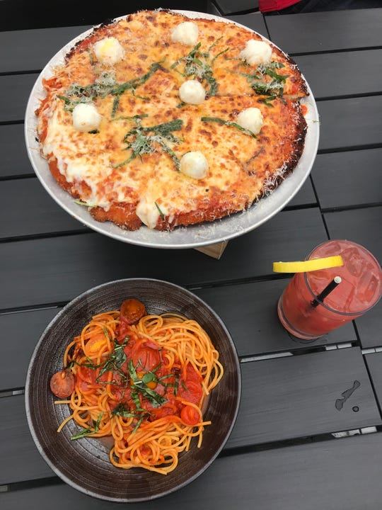 Chicken parmesean pizza for two at Wood & Fire in Scarsdale comes with a side of pasta. Also pictured: the GotWood Lemonade cocktail.