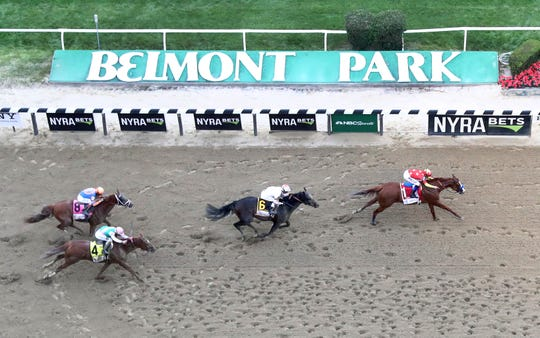 ELMONT, NY - JUNE 09:  Justify #1, ridden by jockey Mike Smith crosses the finish line to win the 150th running of the Belmont Stakes at Belmont Park on June 9, 2018 in Elmont, New York. Justify becomes the thirteenth Triple Crown winner and the first since American Pharoah in 2015.  (Photo by Al Bello/Getty Images)