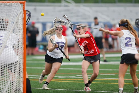 North Rockland's Phoebe Mullarkey takes a shot up on Monroe Woodbury's goalie Megan Petko during Tuesday's Class A regional semifinal in Newburgh on on May 28, 2019.