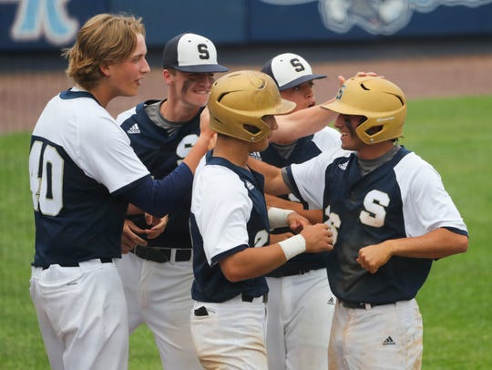 Salesinaum's Zach Kellar is greeted at his dugout after scoring as the Sals break open the game with 5 runs in the fourth inning of Salesianum's 7-1 win in the DIAA Baseball Tournament quarterfinal Wednesday at Frawley Stadium.