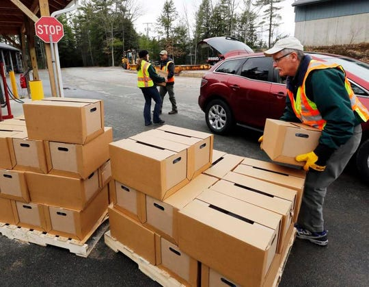 New Hampshire state and local officials load boxes of free bottled water in Litchfield, N.H, in this 2016 photo. New Hampshire is suing eight companies including DuPont for damage it says has been caused statewide by a class of potentially toxic chemicals found in everything from pizza boxes to fast-food wrappers.