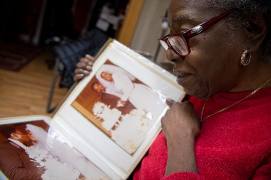 Patricia Blair is overcome with emotion as she looks through her wedding photo album in the living room of her home.