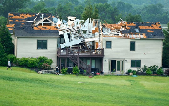 A destroyed home sits in a neighborhood after it was hit by a tornado on May 28, 2019, south of Lawrence, Kan.