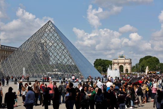 Tourists wait in line to visit the Louvre museum in Paris last year.