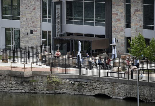 Customers at Tempest Coffee Collective sit on the outdoor patio next to the Fox River in late May.