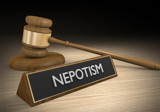 3D render of a wooden court gavel next to a sign that says nepotism.