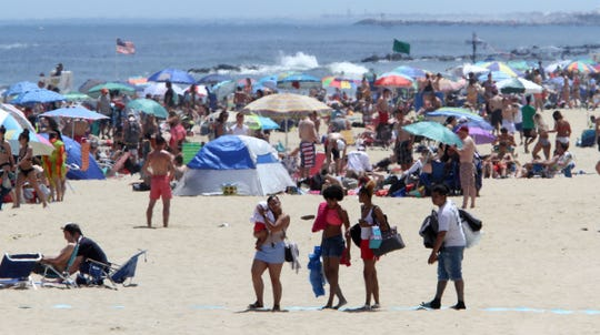 People head out onto the Belmar, NJ, beach on Memorial Day Monday, May 27, 2019.