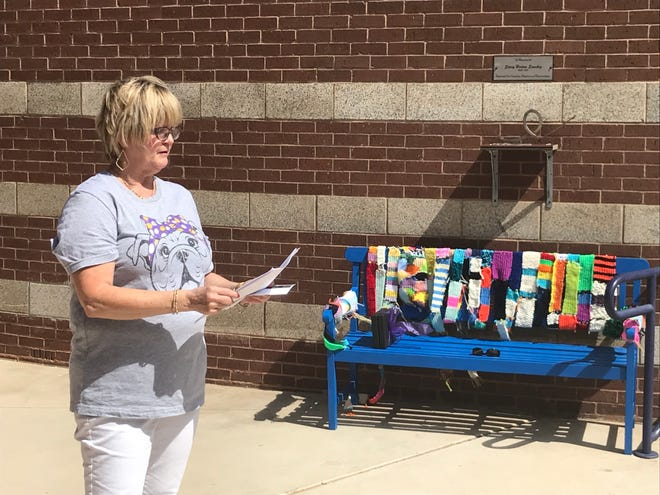 Wylie High School teacher Pam Mauldin comments on her experiences working closely with Stacy Horton Sanchez during a courtyard dedication at the high school in Sanchez's honor Tuesday. Sanchez, an art teacher at the school, died in September after a battle with cancer. The bench, covered by colorful scarves, also is part of the school's tribute to its late teacher.