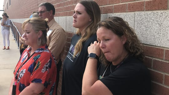 Wylie High School teacher Stephanie Hood, right, wipes away a tear during a dedication ceremony in honor of late teacher Stacy Horton Sanchez on Tuesday. Hood was among more than 30 gathered outside the high school's art courtyard for the ceremony honoring Sanchez.