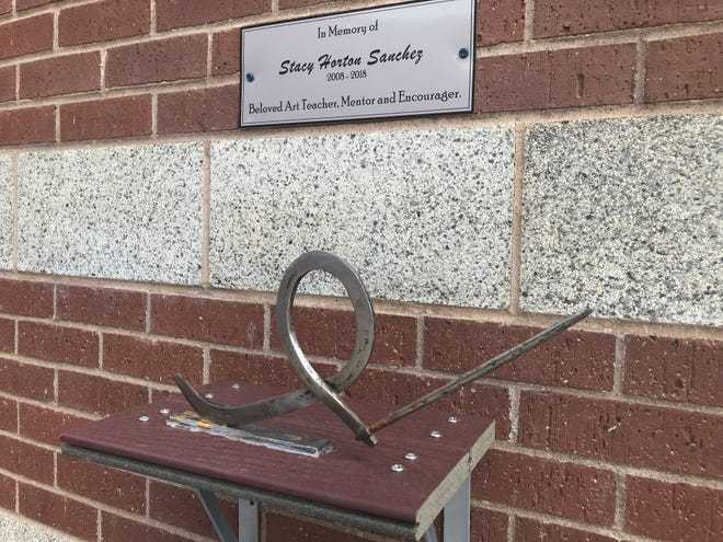A memorial sculpture of an unfinished cancer ribbon and a paintbrush was dedicated in honor of Wylie High School art teacher Stacy Horton Sanchez at the school Tuesday. Sanchez died early in  the school year after a battle with cancer.