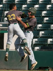 Bryant Espiritusanto, left, and Anthony Zarzana of Melbourne Central Catholic celebrate a run against Cardinal Gibbons in the class 5A state baseball finals on Thursday, May 30, 2019, in Fort Myers.