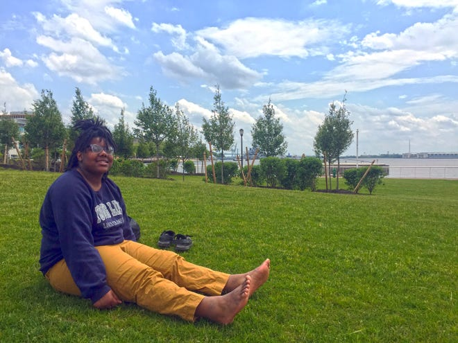 Shaniyla Johnson takes a break and enjoys the view at the new RCA Pier Park along the Camden Waterfront. The park officially opened Thursday.