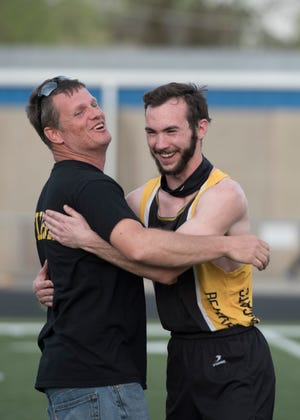 Paint Valley coach Ben Burke, left,  hugs Caleb Adams after Paint Valley's 4x100 relay team wins at the annual Chillicothe Invitational track meet on April 18, 2019.