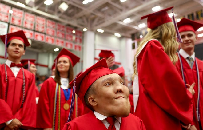 Migdiel Ortiz stands proudly between classmates before approaching the stage to receive his diploma for graduating at APSU Dunn Center in Clarksville, Tenn., on Saturday, May 25, 2019.