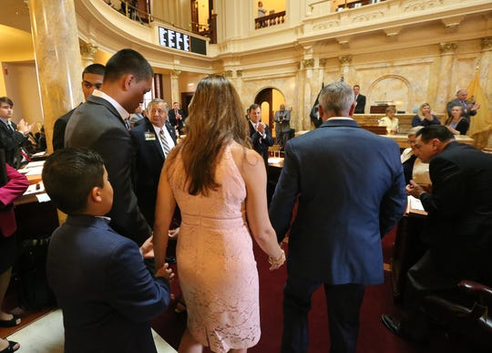 The family of Michael Sot heads to the senate floor as the full senate rises for a standing ovation following the reading of a resolution in his honor