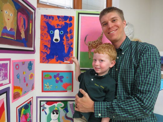 Carter Modes of Berkeley Heights proudly displays artwork to his father, Upper School chemistry teacher Kyle Modes, at the Lower School Art Show.